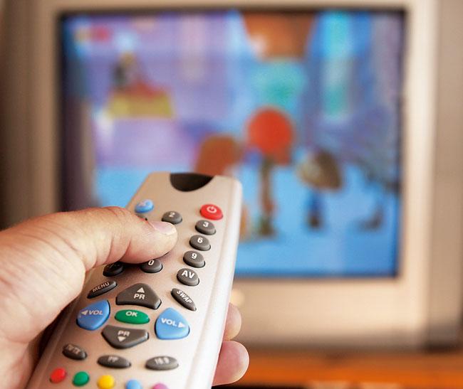 Finger an der Fernbedienung eines Fernsehers