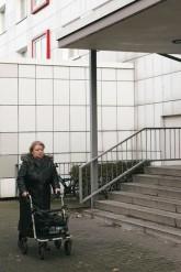 Frau mit Rollator vor einer Hauseingangs-Treppe