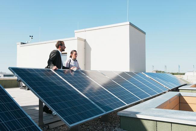 Personen blicken über Solarkollektoren auf dem Dach eines Gebäudes