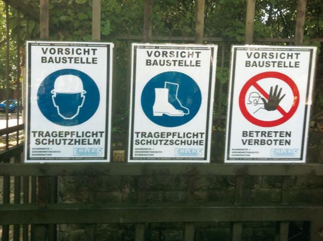 Drei Schilder 'Vorsicht Baustelle' an einem Gartenzaun