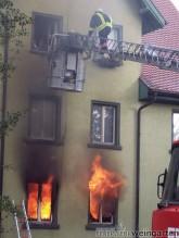Feuerwehr beim Löschen eines Wohnhauses, Flammen schlagen aus den Fenstern