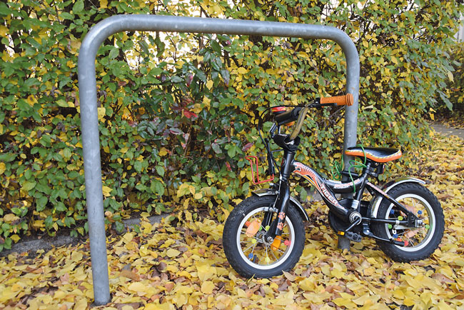 Kinderfahrrad lehnt an Fahrradbügel für 'erwachsene' Fahrräder