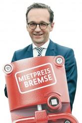Justizminister Heiko Maas hält symbolisch eine 'Mietpreisbremse'