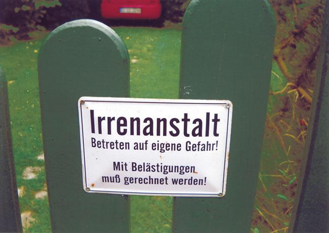 Schild am Gartenzaun mit der Aufschrift: Irrenanstalt - Betreten auf eigene gefahr! Mit Belästigungen muß gerechnet werden!