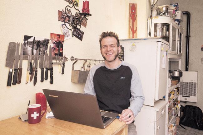Christoph Baumgarten am Laptop in seiner Küche