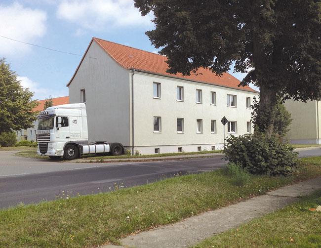 LKW parkt dicht an Hausfassade