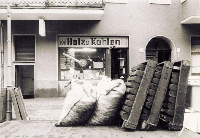 Brikett-Kiepen und Säcke mit Brennholz vor einer historischen Brennstoffhandlung