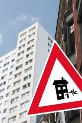 Stoppschild mit einem Wohnhaus, aus dessen Tür ein Mensch herausgeworfen wird