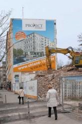 Abrissbagger vor einem Großplakat für einen Neubau