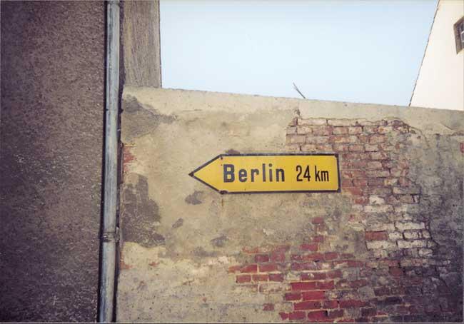 Hinweisschild an Hausmauer: Berlin 24 km