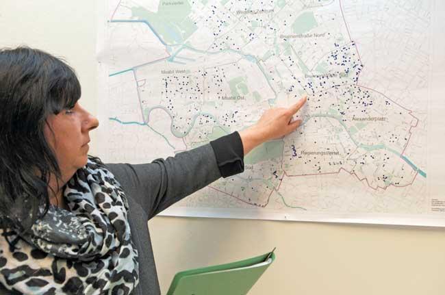 Mitarbeiterin des Bezirksamts Berlin-Mitte vor einer Karte mit fehlbelegten Wohnungen