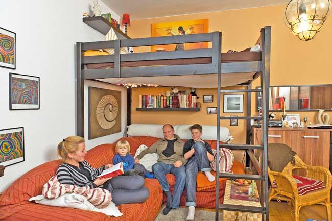 Familie im Wohnbereich unterhalb eines Hochbettes