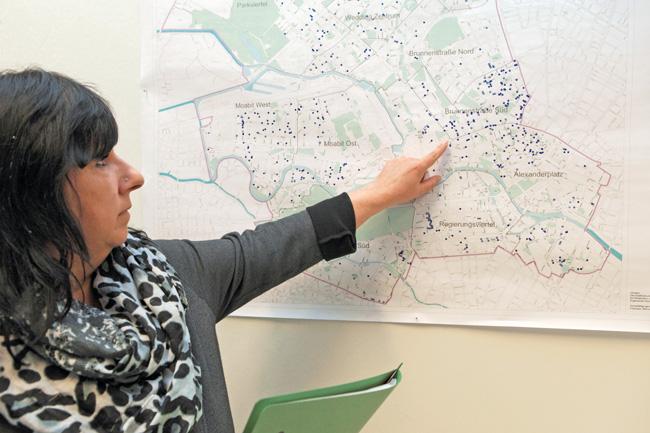 Sachbearbeiterin vor einer Berlin-Karte mit Markierungen