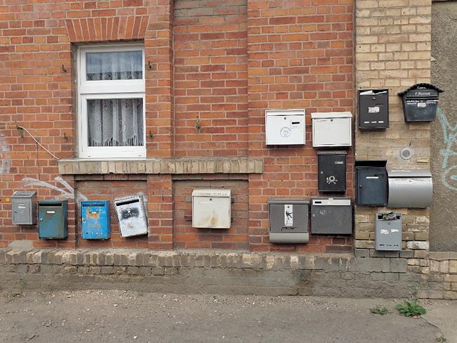 Viele verschiedene Briefkästen an einer Hauswand
