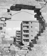 Blick durch ein Mauerloch auf Wohngebäude