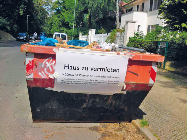 """Leserfoto September 2016 - Container voller Müll mit einem Plakat """"Haus zu vermieten"""""""