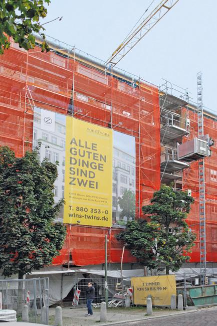 Eingerüstetes Haus mit einem großen Werbeplakat