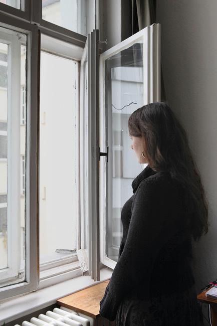 Frau an einem Kastendoppelfenster