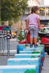 Kind balanciert über farbig gestaltete Poller