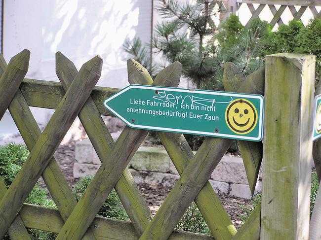 """Leserfoto November 2016 - Jägerzaun mit einem Schild """"Liebe Fahrräder, ich bin nicht anlehnungsbedürftig! Euer Zaun"""
