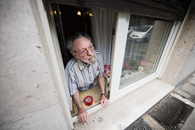 Raucher Adolfs am Fenster seiner Wohnung
