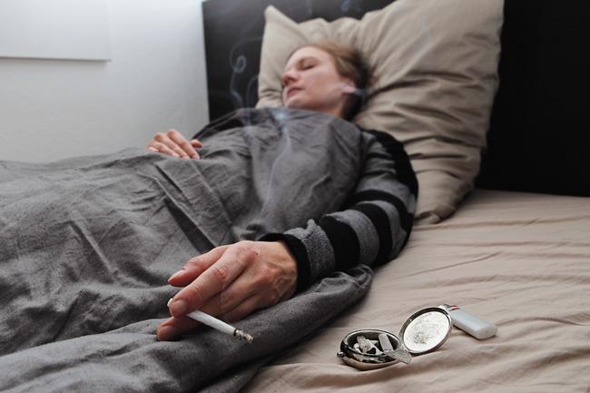 Im Bett rauchende Person