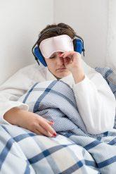 Gestörte Nachtruhe - Person mit Kopfhörer und Augenschutz im Bett