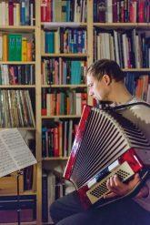 Akkordeonspieler in der häuslichen Bibliothek