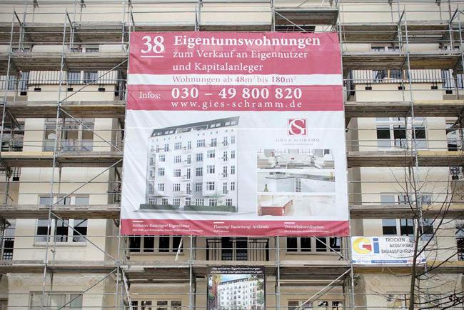 Plakatwerbung für Eigentumswohnungen am Baugerüst