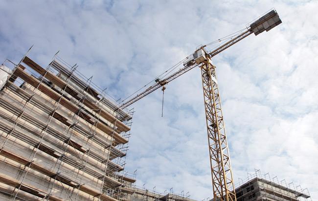 Eingerüsteter Neubau mit Baukran