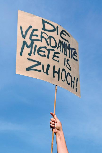 Protestschild mit der Aufschrift: Die verdammte Miete ist zu hoch!