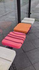 Verschiedenfarbige Sitzkissen in einem Wartehäuschen