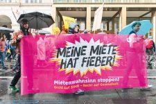 Demonstranten mit Transparent 'Meine Miete hat Fieber!'