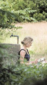 Lesende an Brunnen gelehnt