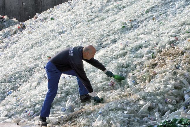 Mann auf einem Kunststoffmüll-Berg