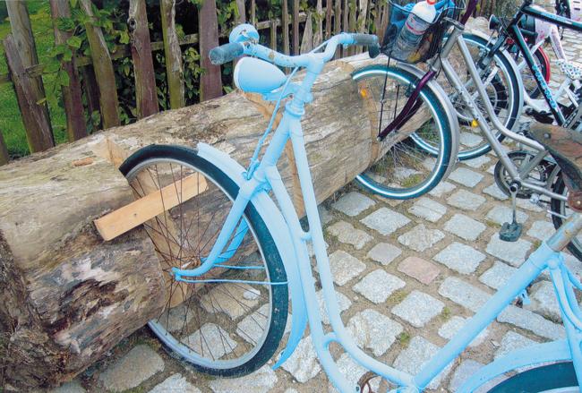 Blaue Fahrräder in einem Baumstamm-Fahrradständer