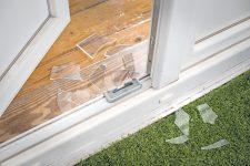 Zerschlagene Balkontür und Glasscherben