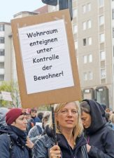 Demonstrantin mit Protestplakat