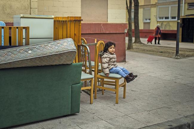 Kind zwischen Umzugsmöbeln