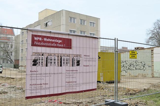 Bauzaun und Plakat mit Neubauplanung