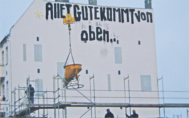 """Betonierkübel am Kranhaken vor einer Brandwand mit aufgesprühtem Schriftzug """"Allet Gute kommt von oben ..."""""""