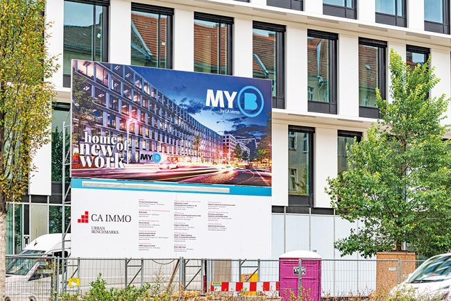 Immobilienplakat vor einem Neubau