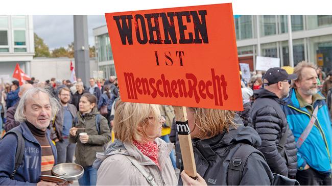 Demonstranten mit Plakat ,Wohnen ist Menschenrecht'