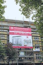 Wohngebäude mit Werbeplakat für Eigentumswohnungen