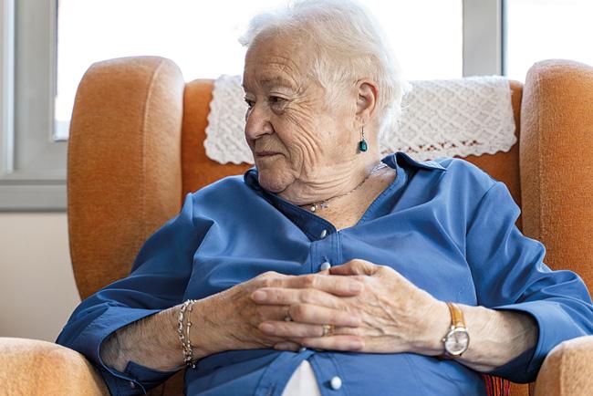 Seniorin im Sessel sitzend