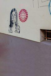 Wandzeichnung: Frau mit Mundschutz und Corona-Signet
