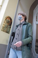 Mann mit Maske vor Hauseingang