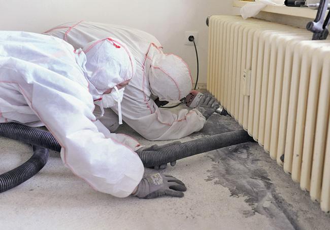 Beseitigung asbesthaltiger Bauteile unter dem Heizkörper