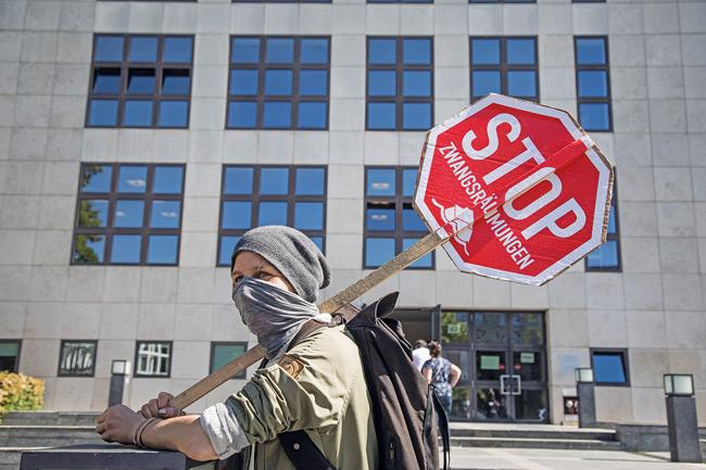 Protest mit Demo-Schild ,Stop Zwangsräumungen'