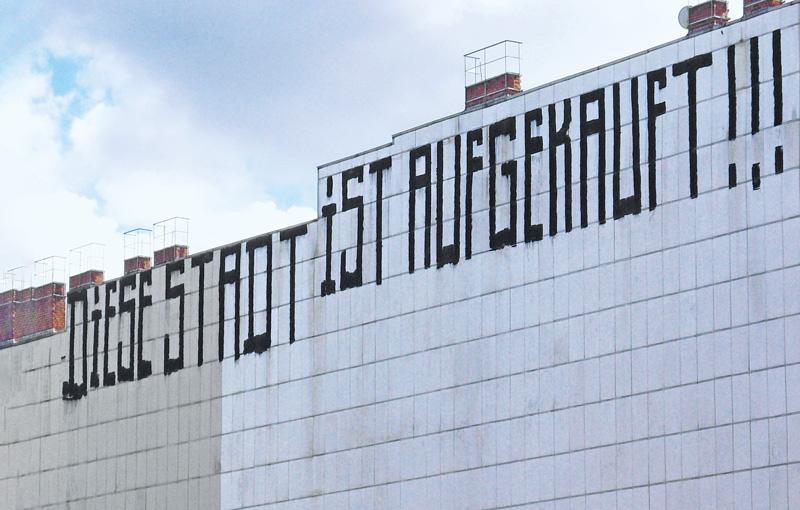 Schriftzug auf Hauswand: Diese Stadt ist aufgekauft!